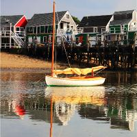 Catboat And Cottage Wharf Reflections