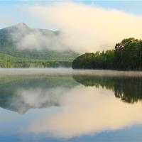 Clouds And Mountain Landscape Reflections On White Lake
